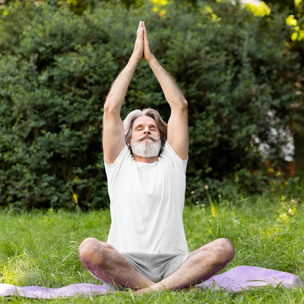 Full shot man doet yoga Gratis Foto