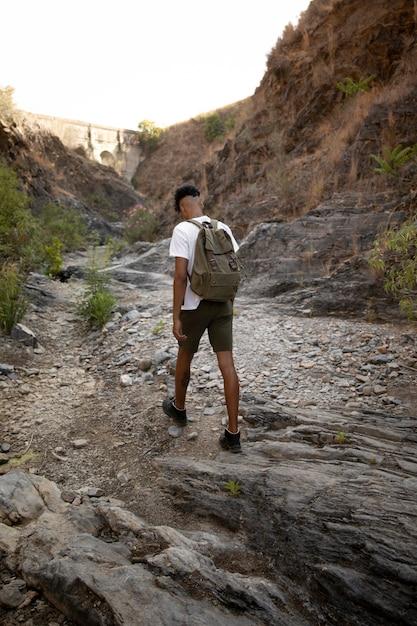 Full shot man lopen met rugzak Gratis Foto