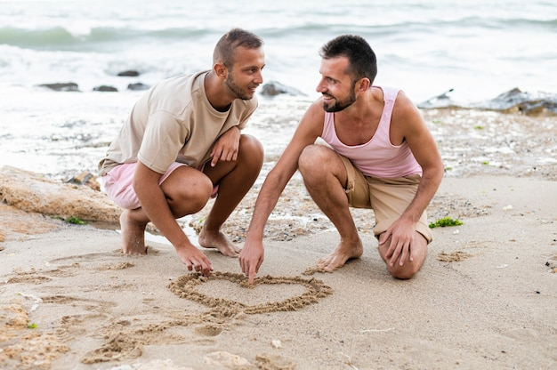 Full shot partners hart tekenen op zand Gratis Foto