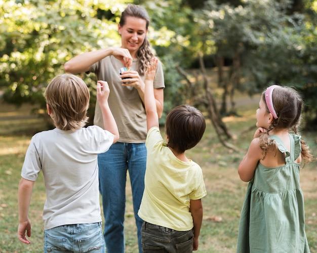 Full shot smiley leraar en kinderen buiten Gratis Foto