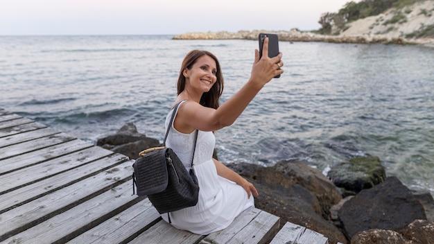 Full shot smiley vrouw selfie te nemen Premium Foto