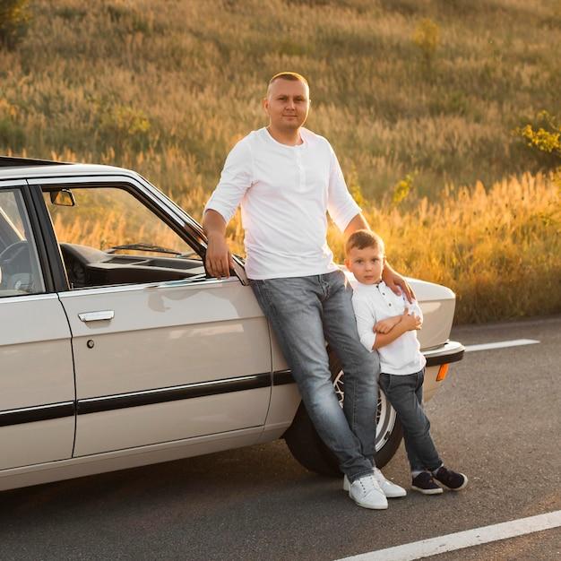 Full shot vader en kind poseren met auto Gratis Foto