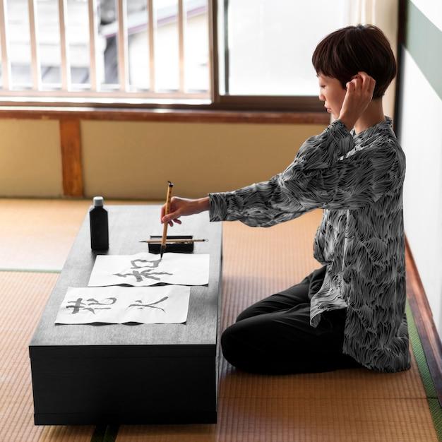 Full shot vrouw schilderij binnenshuis Gratis Foto