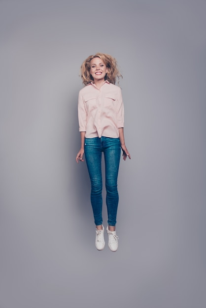 Full size verticaal portret van mooi meisje, gekleed in casual shirtjeans vliegende lucht Premium Foto