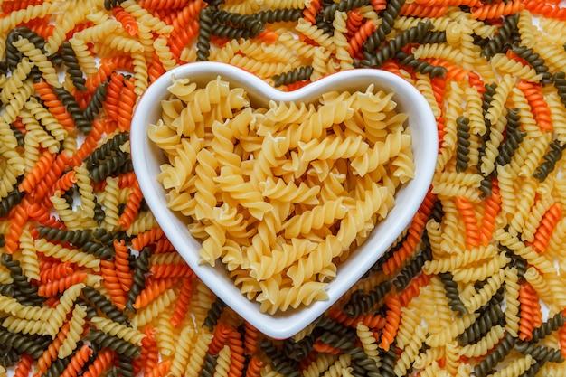 Fusilli pasta in een hartvormige kom op macaroni tafel, plat lag. Gratis Foto