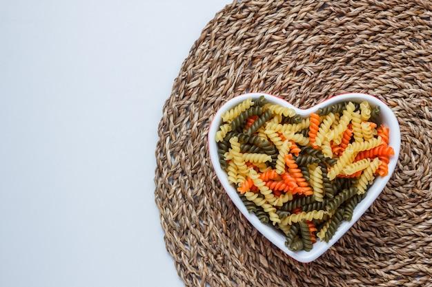 Fusilli pasta in een hartvormige kom op witte en rieten placemat tafel. bovenaanzicht. Gratis Foto