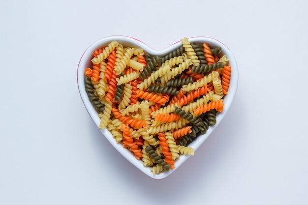 Fusilli pasta in een hartvormige kom op witte tafel, bovenaanzicht. Gratis Foto