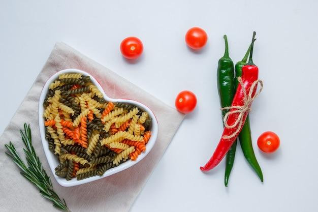 Fusilli pasta in een kom met paprika, tomaten, groene plant bovenaanzicht op wit en gevouwen tafellaken tafel Gratis Foto