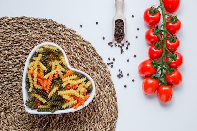 Fusilli pasta in een kom met tomaten, peper in lepel bovenaanzicht op witte en rieten placemat tafel Gratis Foto