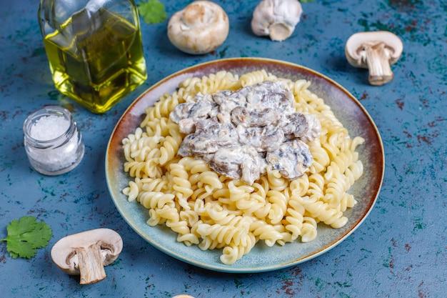 Fusilli pasta met champignons en kip, bovenaanzicht Gratis Foto