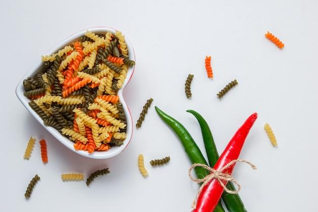 Fusilli pasta met hete pepers in een kom op witte tafel, bovenaanzicht. Gratis Foto