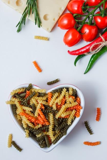 Fusilli pasta met tomaten, paprika's, plant, kaas in een kom op witte tafel, bovenaanzicht. Gratis Foto