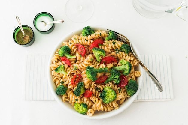Fusilli pastasalade met tomaat en broccoli op servet Gratis Foto