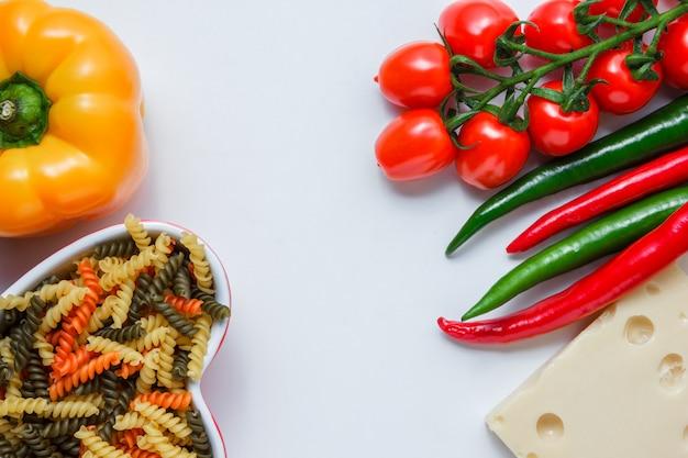Fusillideegwaren met tomaten, peper, kaas in een kom op witte lijst, hoge hoekmening. Gratis Foto