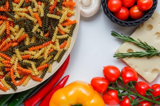 Fusillideegwaren met tomaten, peper, paddestoel, installatie op kaas in een plaat op witte lijst, hoge hoekmening. Gratis Foto