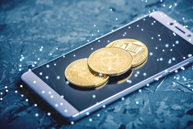 Fysieke bitcoin-munt op het telefoonscherm. het concept van cryptocurrency en blockchain Premium Foto