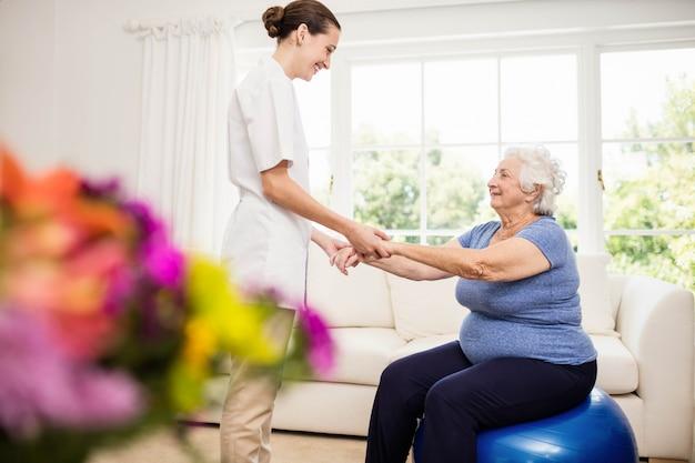 Fysiotherapeut die thuis voor zieke bejaarde patiënt zorgen Premium Foto