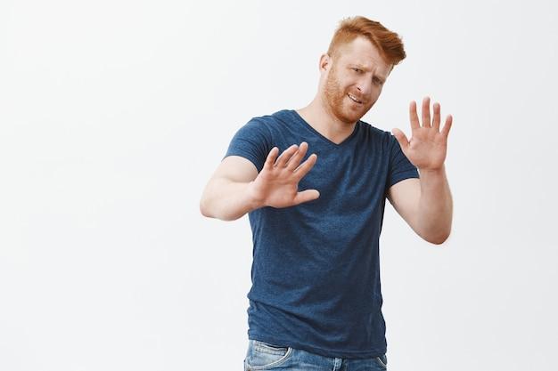 Ga niet bij mij weg. ontevreden ongeïnteresseerde kieskeurige roodharige mannelijke ondernemer in blauw t-shirt, handen trekken in weigeringsgebaar, fronsen gehinderd, afwijzing geven, aanbod afwijzen Gratis Foto