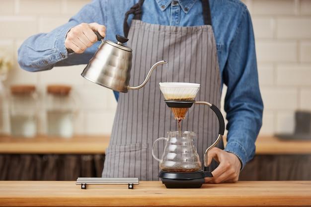Gadgets voor het zetten van koffie. mannelijke barman die pouron koffie brouwen bij bar. Gratis Foto