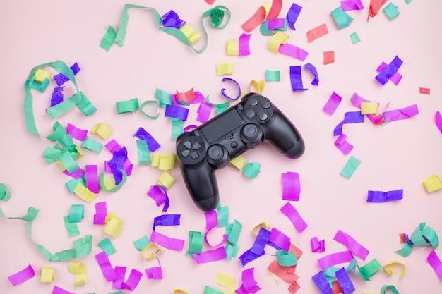 Gamepade ligt in een veelkleurig klatergoud op een roze achtergrond Premium Foto