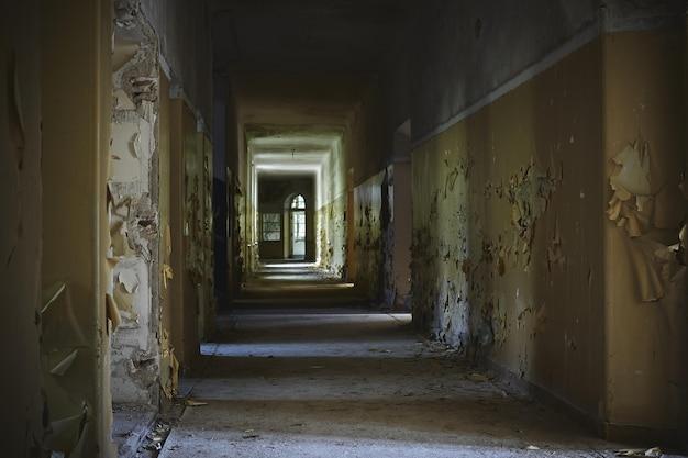 Gang van een verlaten gebouw met oude muren onder de lichten Gratis Foto