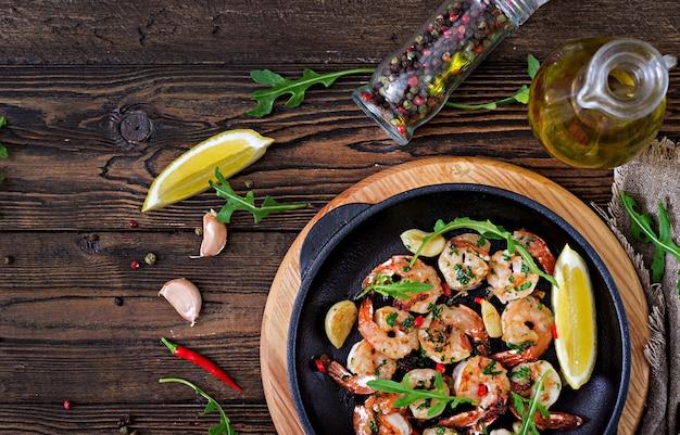 Garnalen garnalen geroosterd in kruidenboter met citroen en peterselie op houten tafel. gezond eten. bovenaanzicht plat leggen. Premium Foto