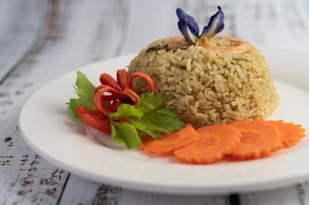 Garnalen gebakken rijst op een witte plaat bestaande uit tomaten en wortelen. Gratis Foto
