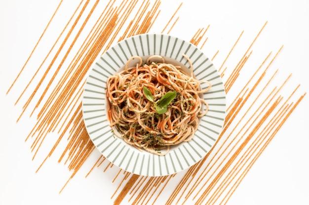 Garneer spaghettideegwaren met ruwe deegwaren op witte oppervlakte Gratis Foto