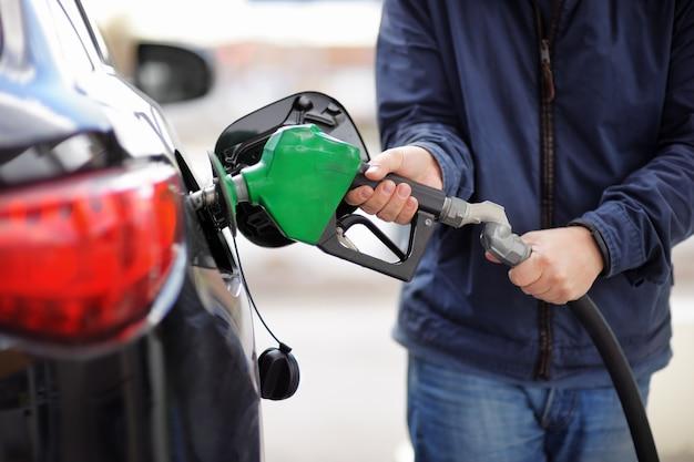 Gas pompen bij een benzinepomp. close-up van brandstof van de mensen de pompende benzine in auto bij benzinestation. Premium Foto