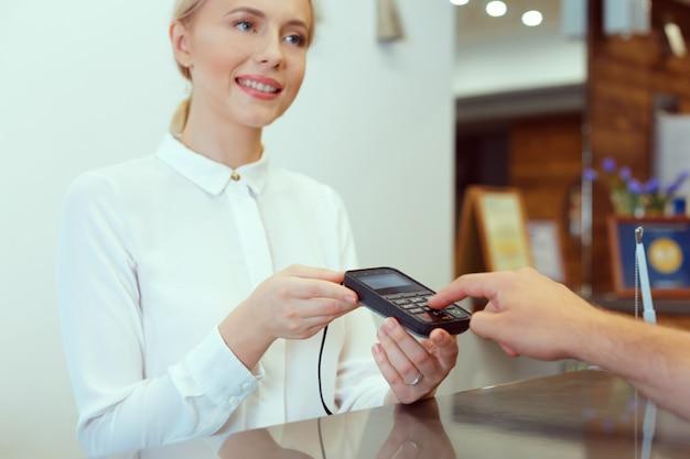 Gast bij hotelreceptie betalen met check tijdens het inchecken Premium Foto