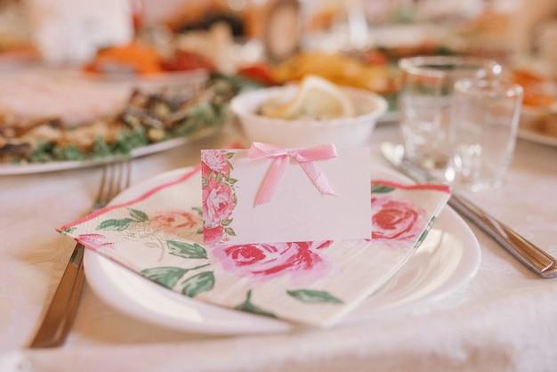 Gastkaart met roze bloemen op de banket bruiloft tafel. bruiloft decoratie Premium Foto