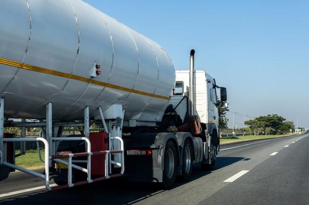 Gasvrachtwagen op wegweg met tankoliecontainer, vervoer op de asfaltuitgang met blauwe hemel Premium Foto