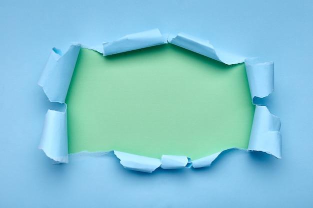 Gat in het blauwe papier. gescheurd. groen samenvatting Premium Foto