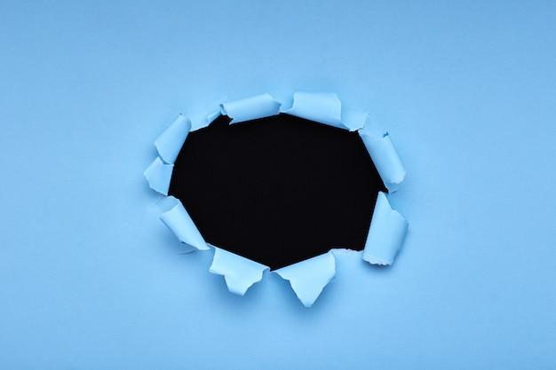 Gat in het blauwe papier. gescheurd. zwart houten. abstract Premium Foto
