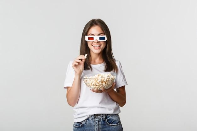Geamuseerde mooie jonge vrouw in 3d-bril films of tv-series kijken, popcorn eten en opgewonden glimlachen. Gratis Foto