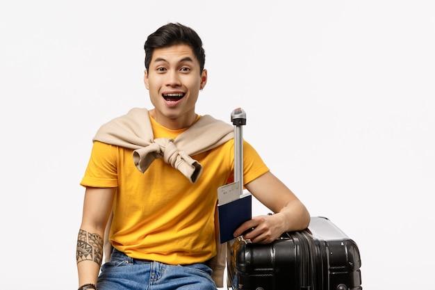 Geamuseerde, vrolijke knappe aziatische jonge mannelijke student reist eindelijk naar het buitenland vrienden, wachtend op de luchthaven, zittend met zwarte koffer, ingepakte bagage en glimlachend dromerig, witte muur Premium Foto