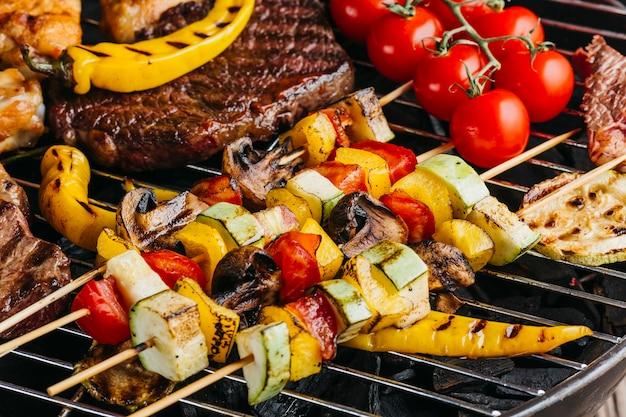 Geassorteerd heerlijk geroosterd vlees met groenten op barbecue Gratis Foto