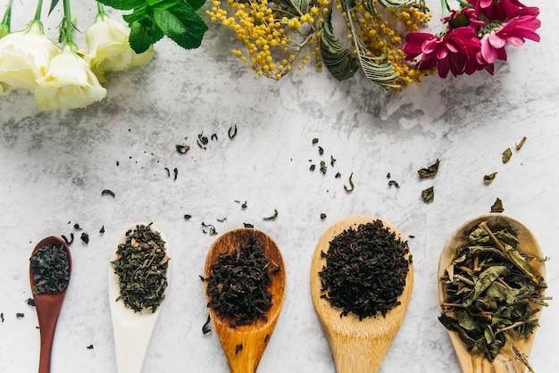Geassorteerde droge medische kruidenthee met bloemen op concrete achtergrond Premium Foto
