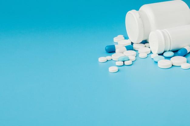 Geassorteerde farmaceutische geneeskundepillen, tabletten en capsules en fles op blauwe achtergrond. kopieer ruimte voor tekst Premium Foto