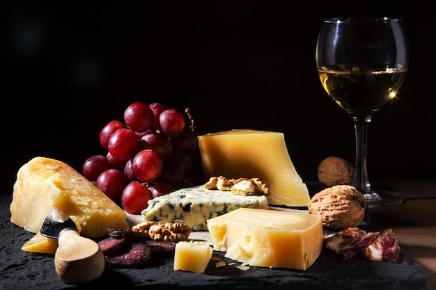 Geassorteerde kazen, noten, druiven, fruit, gerookt vlees en een glas wijn op een serveertafel Premium Foto