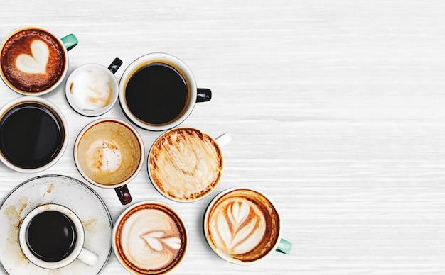 Geassorteerde koffiekoppen op een geweven achtergrond Gratis Foto
