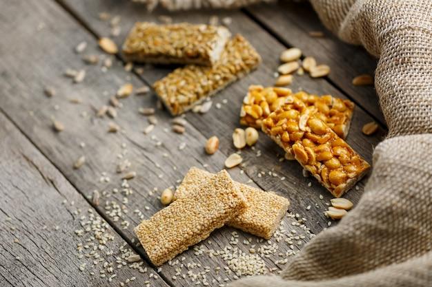 Geassorteerde kozinaki ,, met jute stof. landelijke stijl. heerlijke zoetigheden van de zaden van zonnebloem, sesam en pinda's, bedekt met glanzend glazuur. Premium Foto