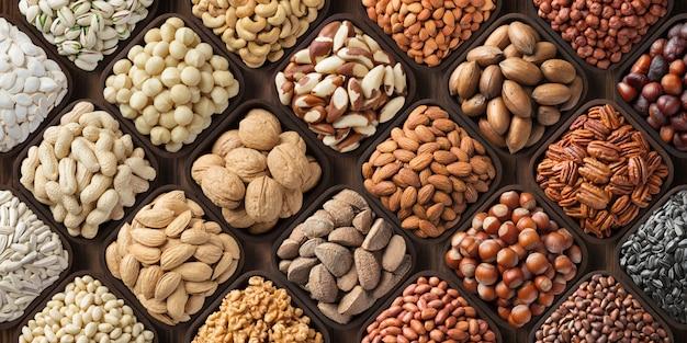 Geassorteerde notenachtergrond, grote mengelingszaden. rauwkostproducten: pecannoten, hazelnoten, walnoten, pistachenoten, amandelen, macadamia, cashewnoten, pinda's en andere Premium Foto