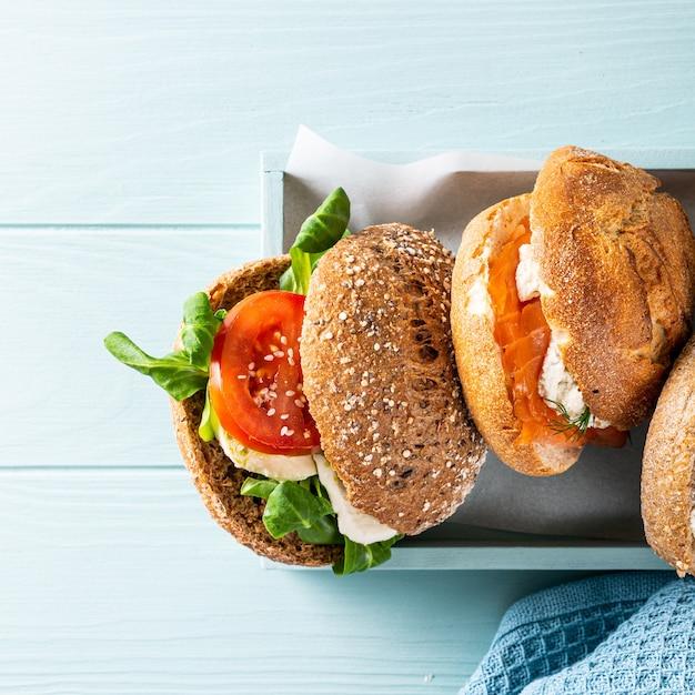 Geassorteerde sandwiches in houten kist op blauwe houten oppervlak. gezond voedselconcept met exemplaarruimte. bovenaanzicht Premium Foto