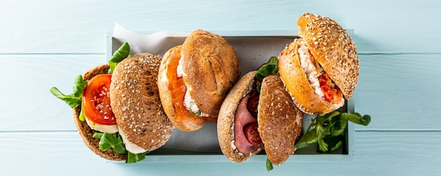 Geassorteerde sandwiches in houten kist op blauwe houten oppervlak. gezond voedselconcept met exemplaarruimte Premium Foto
