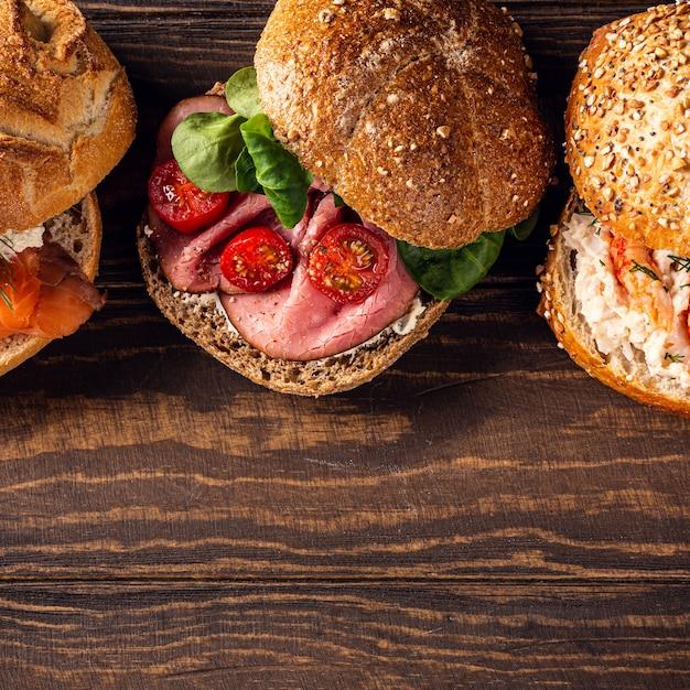 Geassorteerde sandwiches op houten oppervlak. gezond voedselconcept met exemplaarruimte. bovenaanzicht Premium Foto
