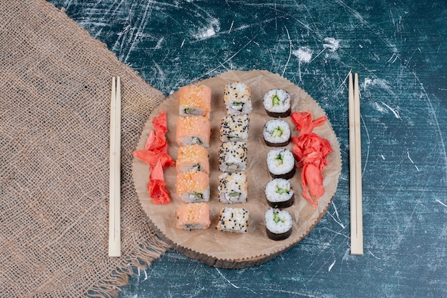 Geassorteerde sushibroodjes die op houten schotel met ingelegde gember en eetstokjes worden gediend. Gratis Foto