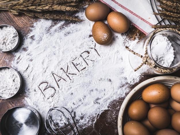 Gebak bakken accessoires bakkerij met bakkerij tekst schrijven op meel. Premium Foto