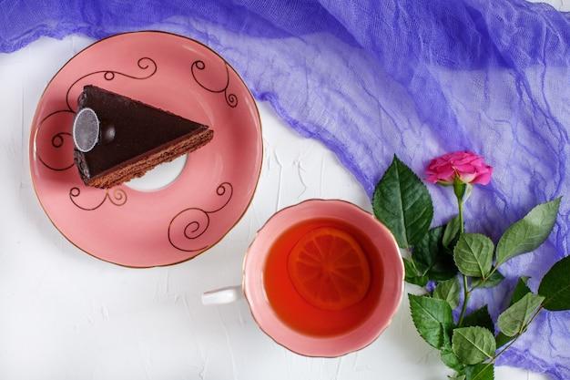 Gebak en hete thee op een dienblad op bilomuuachtergrond. Premium Foto