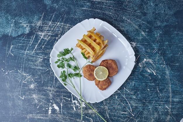 Gebakken aardappelen en nuggets en kruiden. Gratis Foto